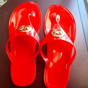 Michael Kors red plastic sandals.